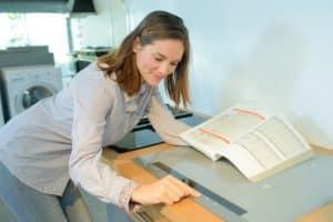 Frau liest Bedienungsanleitung Induktionskochfeld