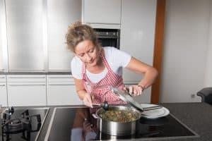 Frau kocht Essen in moderner Küche