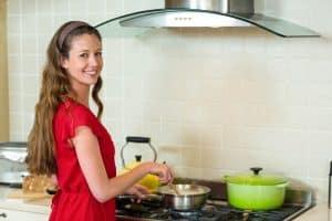 Frau kocht auf Kochfeld mit Abzug