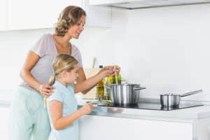Mutter und Tochter kochen am Herd